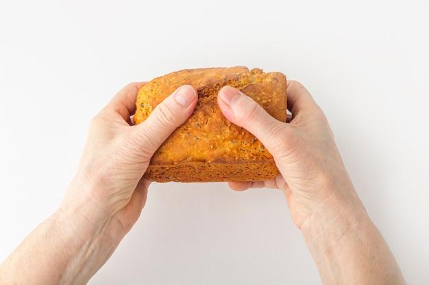 Les mains d'une femme âgée tiennent un petit pain de grains entiers fait maison fraîchement cuit sur une surface blanche. concept de main secourable. copiez l'espace pour le texte