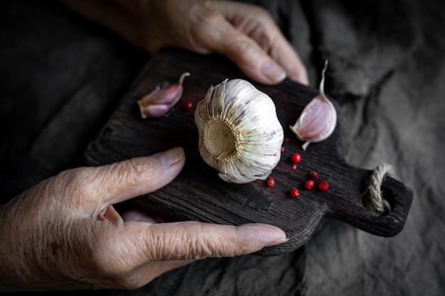 Les mains d'une femme âgée tiennent une planche à découper avec de l'ail en gros plan