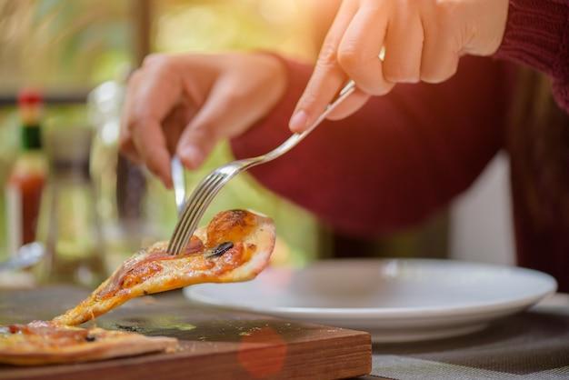 Mains de femme à l'aide de la cuillère et une fourchette en prenant des tranches de pizza.