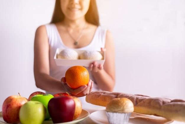Mains de femme asiatique tenant orange et pain sur fond blanc, alimentation saine, concept de régime