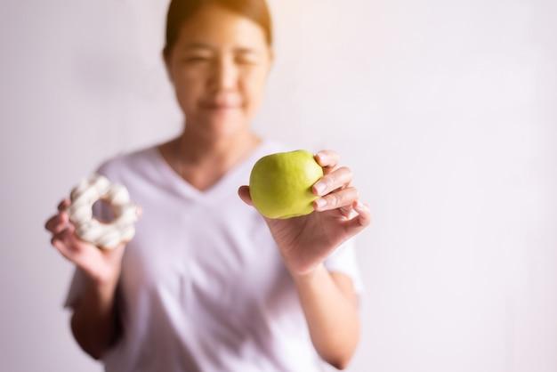 Mains de femme asiatique tenant une pomme verte et un beignet sur fond blanc, alimentation saine, concept de régime