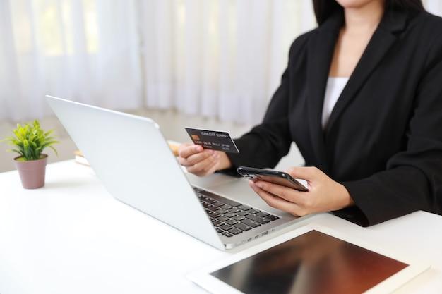 Mains de femme assises et tenant un smartphone et utilisant un ordinateur et une tablette avec carte de crédit
