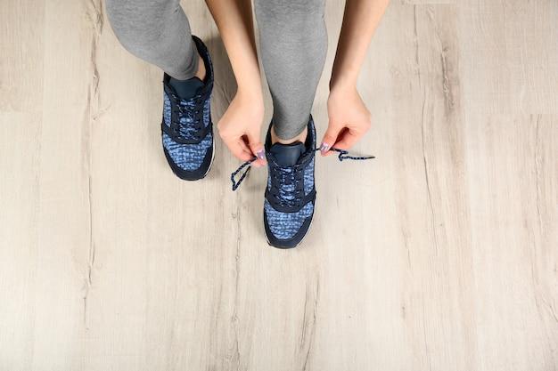 Mains de femme attachant des chaussures de sport