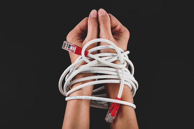 Mains de femme attachées avec un câble réseau
