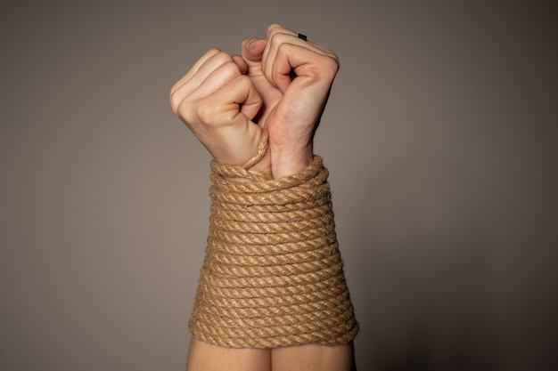 Les mains de la femme attachées avec une corde