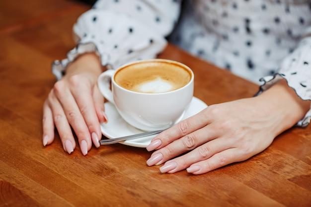 Mains de femme au café avec une tasse de café au lait