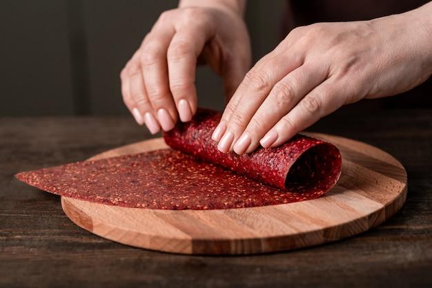 Mains de femme au foyer créative roulant du cuir de fruits fait maison sur planche de bois par table de cuisine tout en faisant des aliments savoureux et sains