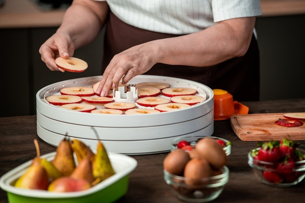 Mains de femme au foyer mettant des tranches de pommes rouges sur un plateau en plastique de séchoir à fruits parmi les poires mûres, les fraises et les kiwis
