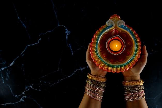 Les mains de la femme au henné tenant une bougie allumée pour le festival de diwali