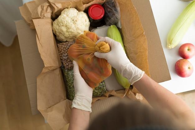 Les mains d'une femme bénévole mettent de la nourriture dans une boîte. livraison par courrier des courses.