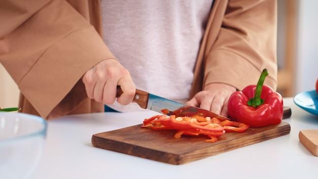 Les mains de la femme bouchent le poivre en tranches sur une planche à découper en bois dans la cuisine. cuisiner la préparation d'aliments biologiques sains heureux ensemble mode de vie. repas gai en famille avec des légumes