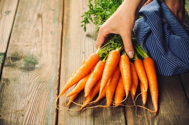 Mains de femme et bouquet de carottes fraîches sur fond rustique
