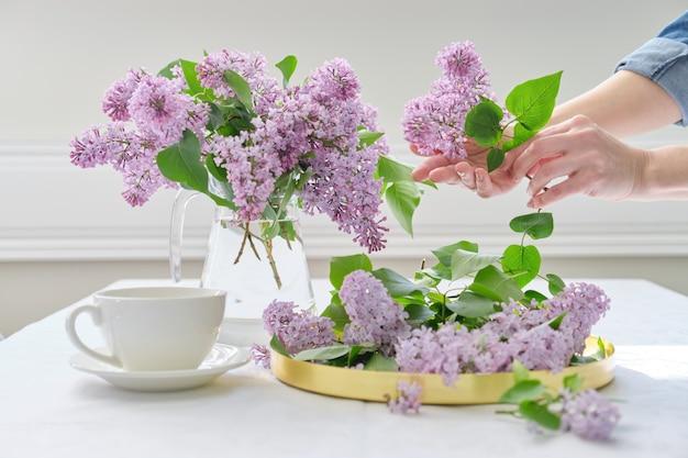 Mains de femme avec bouquet de fleurs lilas dans une cruche en verre