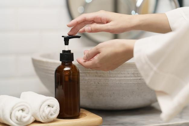Mains de femme avec une bouteille de distributeur de savon à l'évier dans la salle de bain.