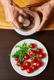 Mains de femme broyant du poivre