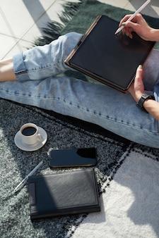 Mains de femme caucasienne s'appuyant sur une tablette numérique, assis sur un plaid. concept indépendant