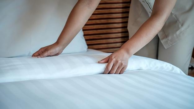Les mains de la femme de chambre de l'hôtel font le lit dans la chambre d'hôtel de luxe