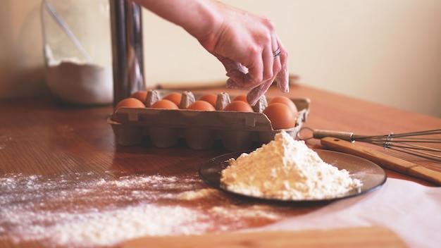 Les mains d'une femme chef cueillant un œuf pour faire de la pâte tout en faisant du pain avec un tas de blé à proximité