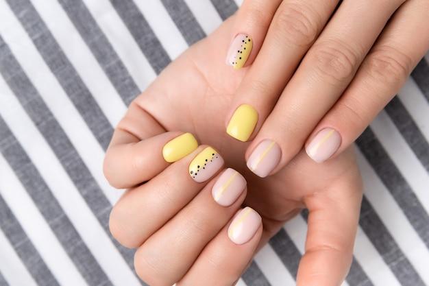 Les mains de la femme avec la conception des ongles printemps-été. manucure féminine à la mode dans un style minimaliste. modèle de salon de beauté