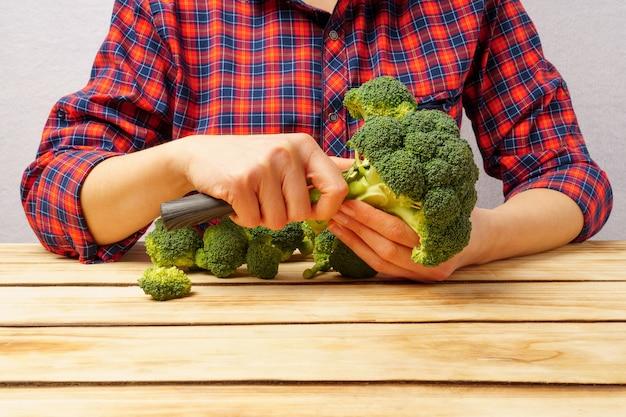 Mains d'une femme coupant le brocoli.