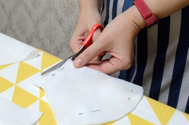 Les mains de la femme coupent le tissu avec des ciseaux selon le motif sur la table.