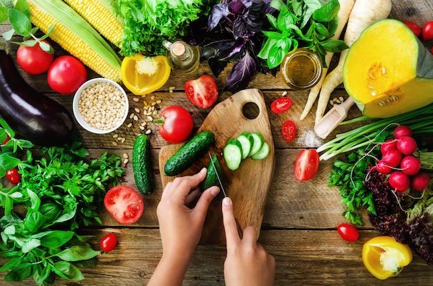 Mains de femme couper les légumes sur fond en bois. ingrédients de cuisson des légumes