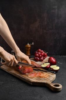 Mains d'une femme couper une tranche de jambon de dinde séchée à l'air sur une planche à découper en bois