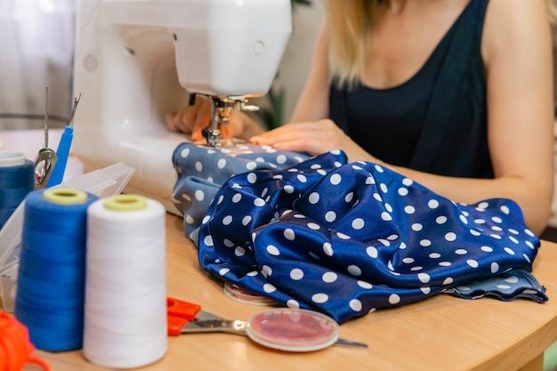 Mains d'une femme couturière travaillant sur une machine à coudre, en flou, mise au point sur le tissu