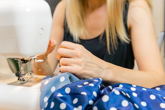Mains d'une femme couturière travaillant sur une machine à coudre, gros plan