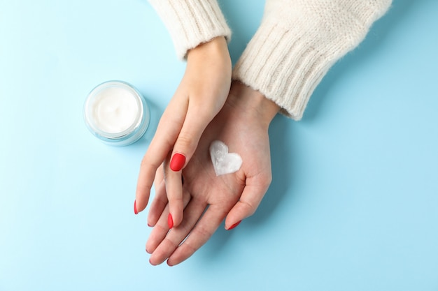 Mains de femme, crème hydratante pour une peau propre et douce en hiver, pot de crème, pull, forme de coeur créé à partir de crème sur bleu, espace pour le texte. vue de dessus. concept de soins de santé