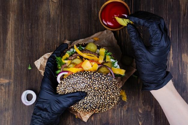 Les mains de la femme dans des gants de caoutchouc noirs tiennent un burger de pain noir juteux