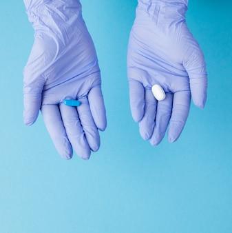 Mains de femme dans des gants médicaux donnant deux grosses pilules