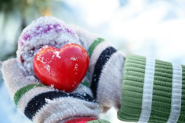 Mains de femme dans des mitaines tricotées tenant un coeur rouge sur fond d'hiver