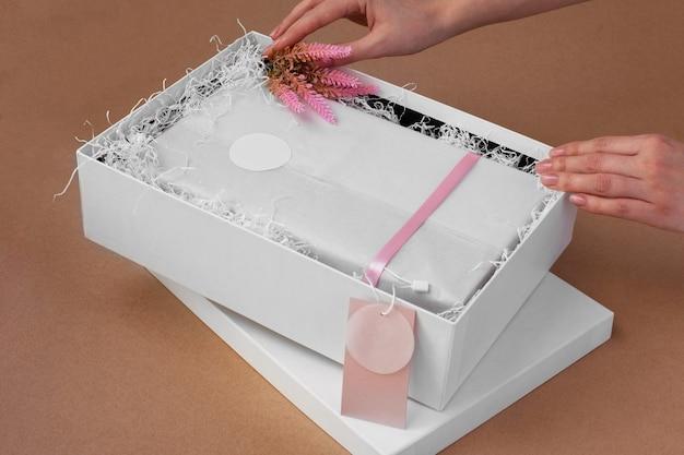 Les mains d'une femme déballent une boîte avec des vêtements et une étiquette vierge rose pour une marque ou un logo et un décor de fleurs roses