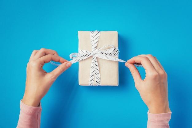 Les mains de la femme délient l'arc sur la boîte-cadeau