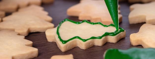 Mains de femme dessinant un biscuit de noël en pain d'épice
