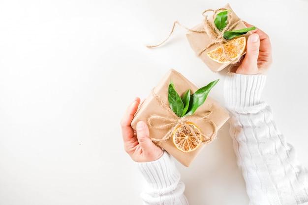 Mains de femme détient des cadeaux de noël décorés rustiques