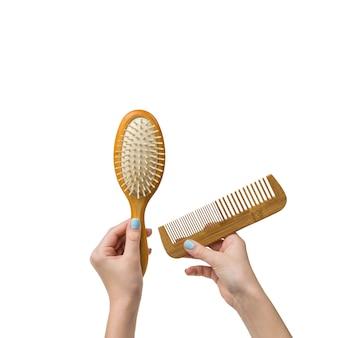 Mains d'une femme avec deux peignes en bois isolés sur fond blanc. outils pour le soin des cheveux.