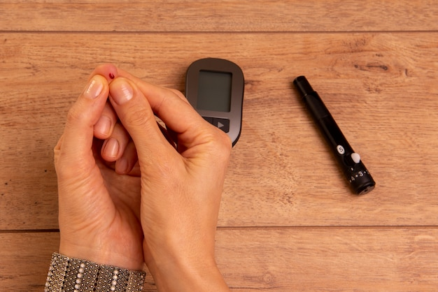 Mains de femme diabétique à l'aide d'un glucomètre pour mesurer la glycémie.
