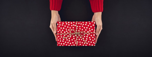 Mains de femme donnant une boîte de cadeau de noël sur fond noir