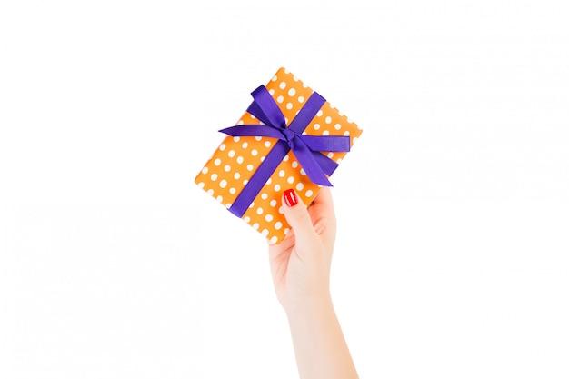 Des mains de femme donnent un cadeau de noël ou autre cadeau à la main emballé dans du papier orange avec un ruban violet.