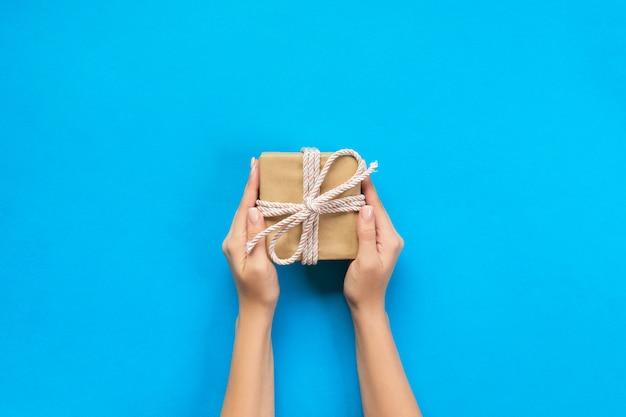 Des mains de femme donnent des cadeaux emballés à la main pour la saint-valentin ou d'autres fêtes en papier avec ruban bleu