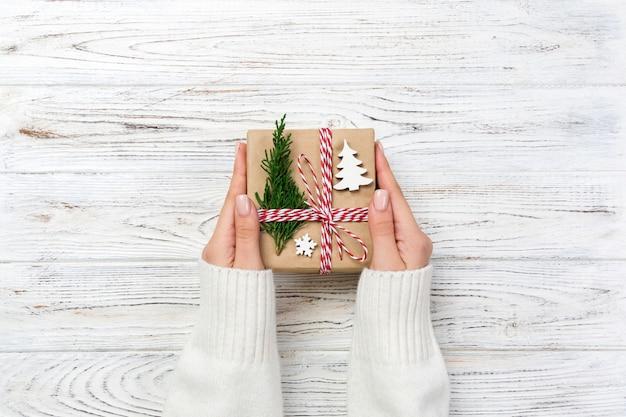 Mains de femme donnent emballé cadeau de noël à la main en vue de dessus de papier,