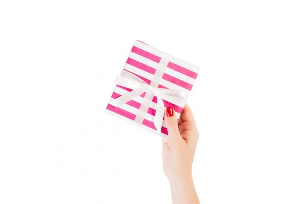 Mains de femme donnent noël enveloppé ou d'autres vacances à la main présent dans un ruban blanc en papier rose. isolé sur blanc, vue de dessus. boîte-cadeau d'action de grâces
