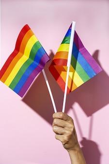 Mains de femme avec drapeau lgbt sur fond rose