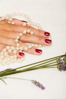 Mains d'une femme avec du vernis à ongles rouge posé par une esthéticienne