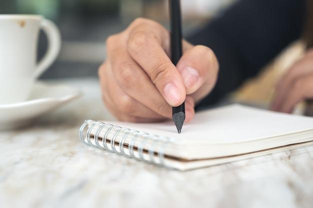 Les mains d'une femme écrivant sur un cahier blanc avec une tasse de café et un dessert