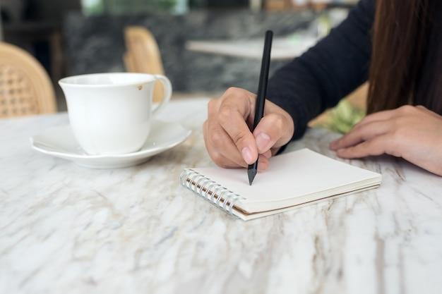 Mains de femme écrivant sur un cahier blanc vierge avec une tasse de café et un dessert sur la table