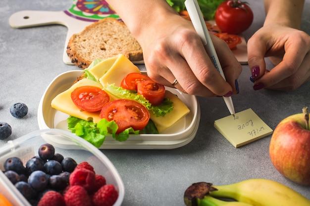 Mains de femme écrivent une note 'avec amour' près de sandwich aux légumes et au fromage sur fond gris