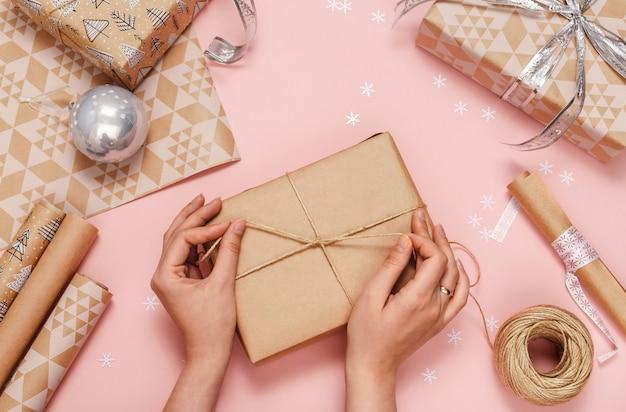 Mains de femme emballant des cadeaux dans du papier kraft. vue de dessus.